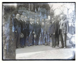 Group portrait of unidentified men outside stone building