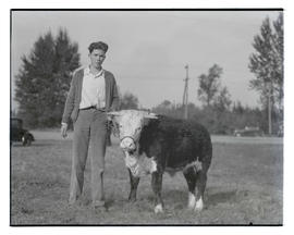 Unidentified member of Sherman County 4-H posing with steer, probably at Pacific International Li...