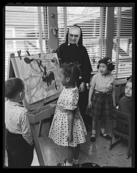 Sister May Dana with children at the Blessed Martin Interracial Day Nursery