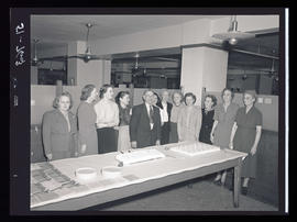 Group of people standing next to table and cake