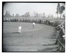 Golfer putting as crowd watches