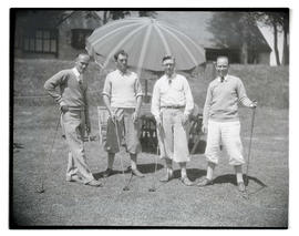 Four golfers holding clubs