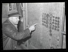 Worker pointing to galvanized metal plate at Albina Engine & Machine Works, Portland
