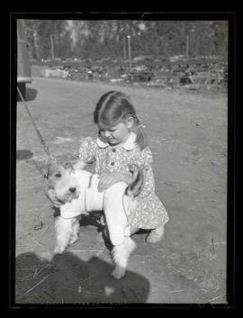 Young girl with dog, probably at Pacific International Livestock Exposition