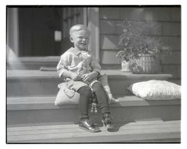Unidentified young boy seated on stairs, full-length portrait