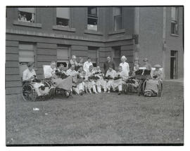Unidentified patients on hospital lawn with boxes of flowers