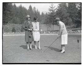 Woman holding golf club as two others watch