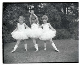 Three young ballet dancers in tutus, posing outdoors