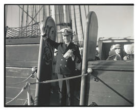 Commander Louis J. Gulliver waving from aboard USS Constitution