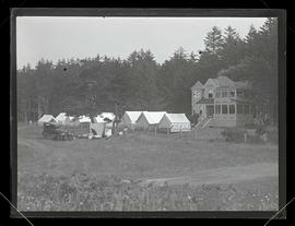 Car and YWCA tents in field next to house