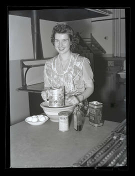 1942 Portland Rose Festival Princess Shirley Fowler posing with baking ingredients