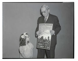 Man showing Portland Community Chest poster to young girl
