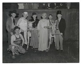 Members of East Side Commercial Club in costume, posing with donkeys