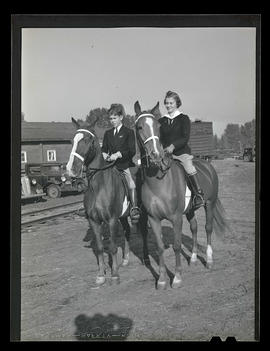 Two riders on horseback, probably at Pacific International Livestock Exposition
