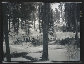 Men camped in the snow with elk crates