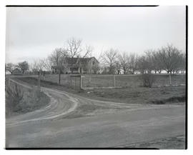 Unidentified two-story house and fenced field in rural area