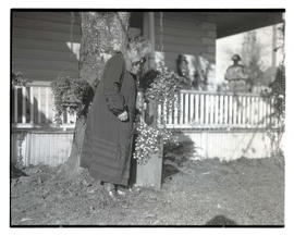 Unidentified woman in yard, looking at potted flowers