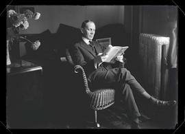 William T. Pangle sitting in chair and reading