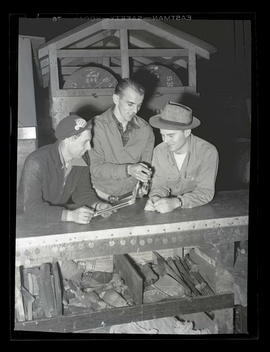 Three workers looking at equipment, Albina Engine & Machine Works, Portland