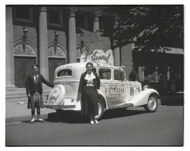 Unidentified man and woman posing with promotional car, 18th and Couch, Portland