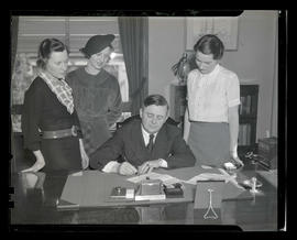 Portland Mayor Joseph K. Carson signing document as three unidentified women watch