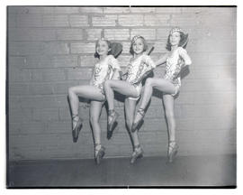Three young ballet dancers in costume, posing en pointe