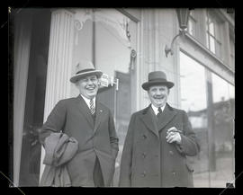Two men outside storefront, half-length portrait