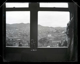 View of unidentified town and hills through window