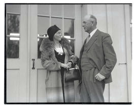 Woman and man outside building, possibly at livestock show