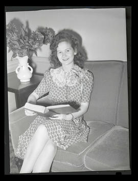 1942 Portland Rose Festival Princess Margaret Ann Tate posing with book