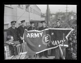 Four Navy servicemen and electrician Ed Mabie holding pennant during award ceremony at Albina Eng...