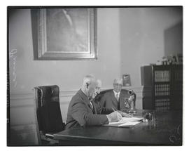 Walter M. Pierce sitting at desk in governor's office; Isaac L. Patterson in background