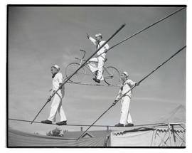 Three men performing high-wire act