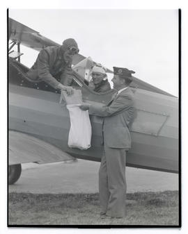 Aviator placing object in sack held by American Legion member