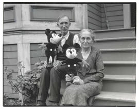 Elias and Flora Disney at their Portland home, holding Mickey Mouse toys