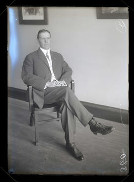 Unidentified man sitting in chair, full-length portrait