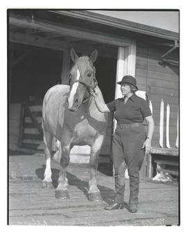 Mrs. E. F. Peffer with Belgian horse, Minnie, probably at Pacific International Livestock Exposition