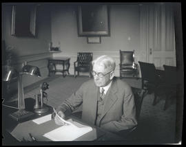 Isaac L. Patterson at desk in governor's office, looking at documents