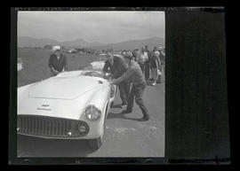Three men pushing Kurtis sports car at auto races in Tillamook, June 1955