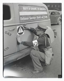 Unidentified man marking Portland Gas & Coke Co. car with civilian defense insignia