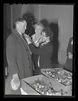 Unidentified woman pinning flower to lapel of unidentified man