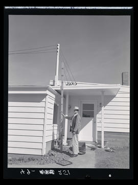 Man with measuring stick next to newly constructed home