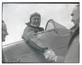 E. E. Spafford in airplane, shaking hands with Mayor George L. Baker