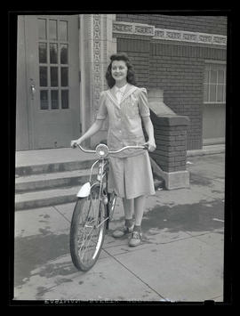 1942 Portland Rose Festival Princess Madelyn Devaney posing with bicycle