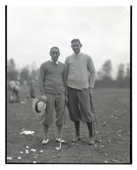 Two golfers posing with clubs