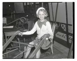 Girl sitting on farm equipment