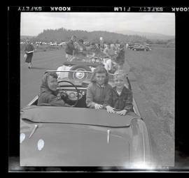 Woman and two children in car at auto races in Tillamook, June 1955