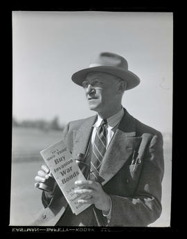 Man holding document and binoculars