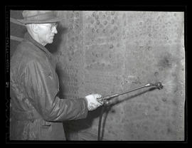 Worker using shrinking equipment on galvanized metal plate at Albina Engine & Metal Works, Po...