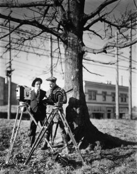 Two cameramen with Kiser Studios in background